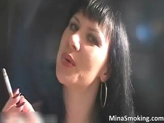 naughty brunette hair hoe smokes a cigarette