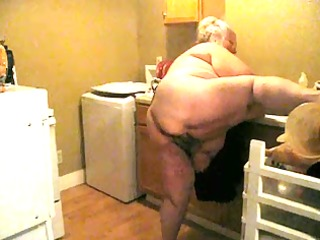 in the kitchen with apron on teasing